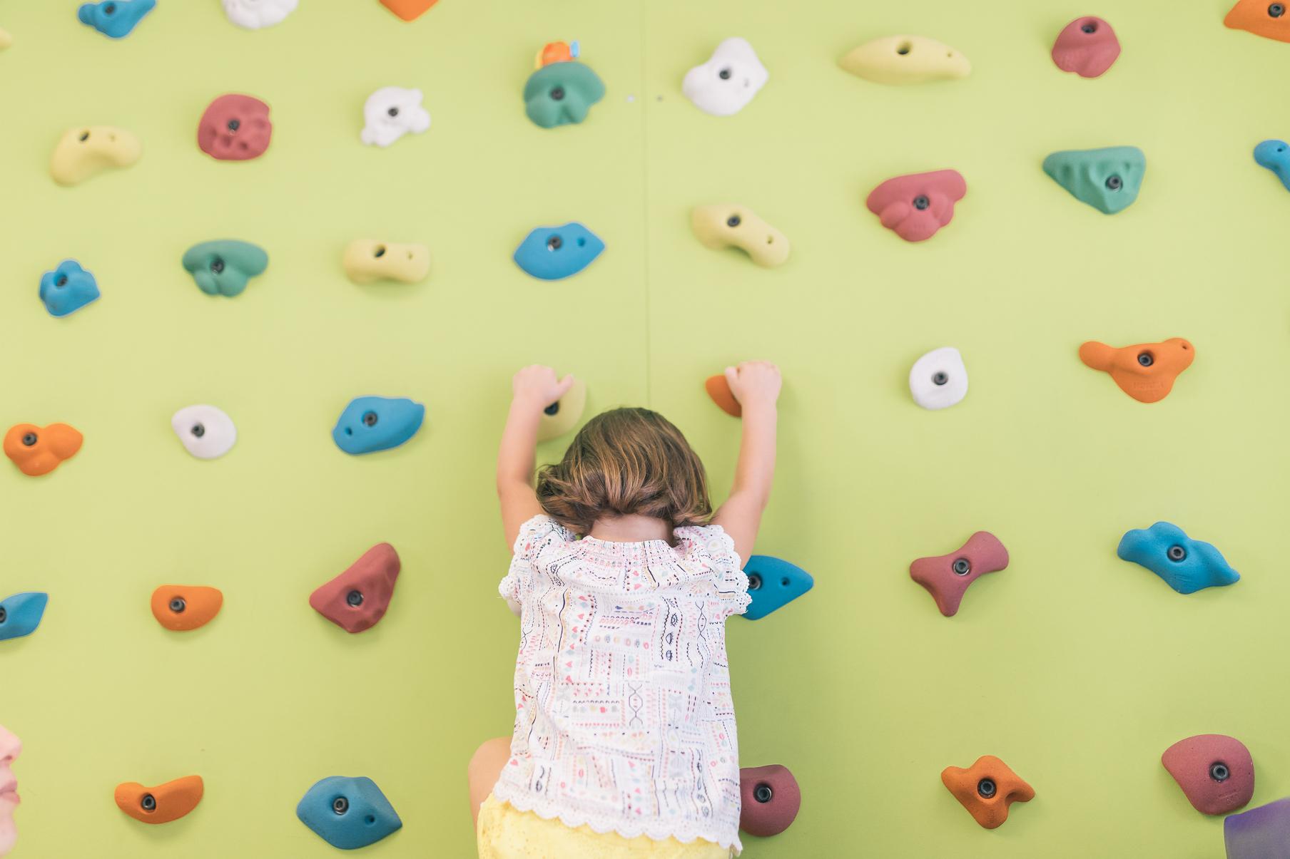 Niño/a escalando rocodromo